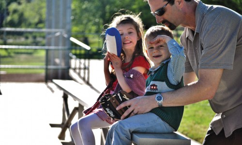Summer sports are nearing: Mark Baskin and his children Emma (left) and Ben (right) catch a CLU baseball game.
