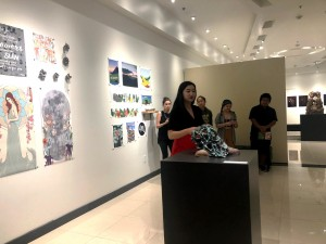 """Senior Hallie Maxwell discusses her art at a walk-through of """"Natural Conditions,"""" an exhibit assembled by the art capstone class, on May 3.  Photo by Lindsey Potter- Reporter."""