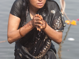 A woman offering up prayers as part of her morning puja on the bathing ghat in Ujjain, Madhya Pradesh.