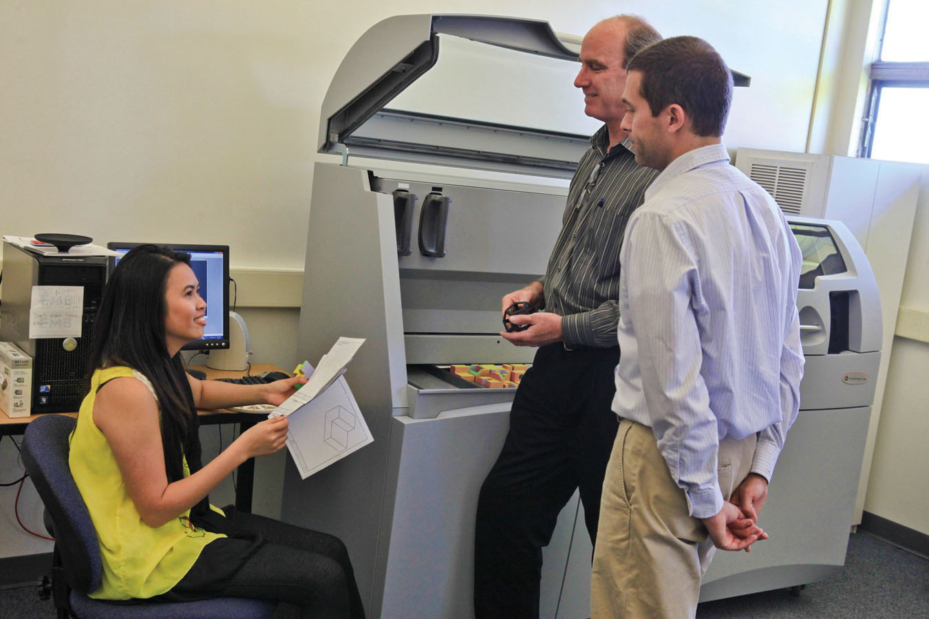 """Sophomore Huong """"Ivy"""" Nguyen, who plans to use the 3-D printer to make platforms for chemical instrumentation, talks with bioengineering and physics lecturer Bob Rumer. Her adviser Grady Hanrahan (r) is the John Stauffer Endowed Professor of Analytical Chemistry and co-director of the Hugh and Hazel Darling Center for Applied Scientific Computing."""