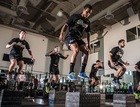 Kingsmen soccer players launch from the Forrest Fitness Center floor. Doing their plyometrics, from left, are Henry Breheny, Logan Cone, Bryan Hulse, Nick Baldi, and Tal Zaiet. (Photo by Brian Stethem '84)