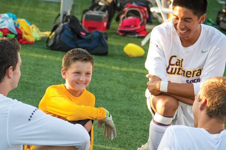 Before a home game in September, Dylan Roslauski and his Cal Lutheran teammates enjoy some time on the sidelines. (Photo by Brian Stethem '84)