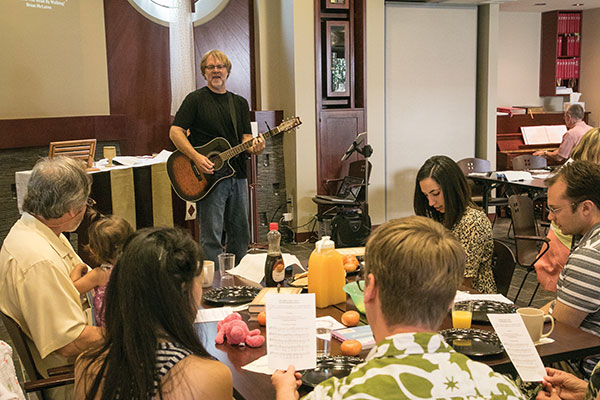 The Rev. Greg Ronning '82, M.Div. '88, cooks and plays guitar for congregants at The Table at the ELCA Pacifica Synod office in Santa Ana, California. He does not deliver a sermon. (Photo by Brian Stethem '84)