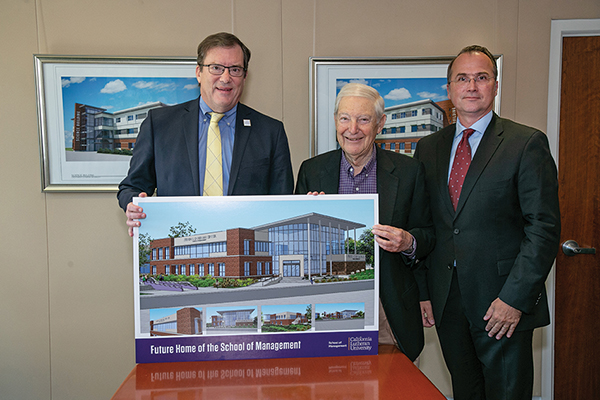 To be built where Nygreen Hall has stood since 1973, the Steven D. Dorfman Center will have six classrooms, a large lecture hall, a computer lab, a community room and gathering spaces on both floors. In the photo, Dorfman (center) meets with President Chris Kimball (left) and Gerhard Apfelthaler, dean of the school, for a signing ceremony.