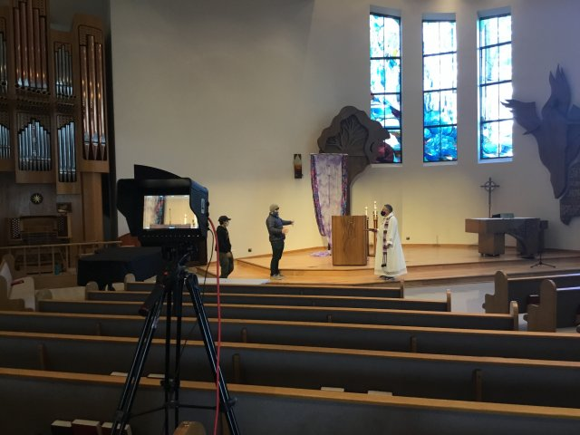 Media Services worker Brandon Perera '20, left, and Media Services coordinator Chris Reynolds-Baldwin '17, help the Rev. Scott Maxwell-Doherty '76, MDiv '81 (PLTS), prepare to film a weekly service at Cal Lutheran's Samuelson Chapel.