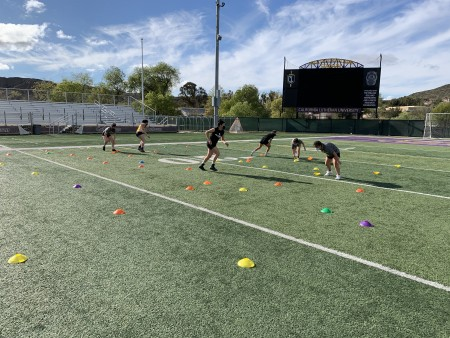 When COVID-19 restrictions eased, women's lacrosse practices involved individual drills with physically distant players wearing face masks.