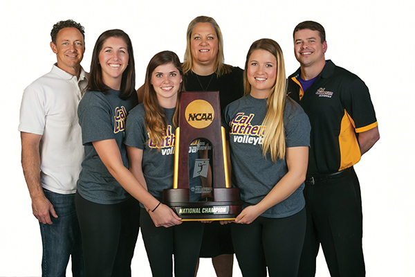Head women's volleyball coach Kellee Roesel (center) is surrounded by her coaching staff. From left: assistant coach/men's volleyball head coach Kevin Judd, assistant coach Kassie Livesey, assistant coach/JV head coach Rachel Smith '13, graduate assistant Kennedy Peters '15 and conditioning coach Patrick Holmberg '03, Ed.D. '11. (Photo by Brian Stethem '84)